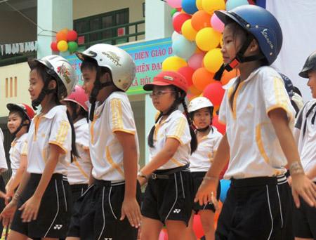 Ngành giáo dục đẩy mạnh nhiều hoạt động tuyên truyền về đội mũ cho học sinh, nhưng kẹt ở chỗ người vi phạm lỗi này là ở phụ huynh. Trong ảnh: Học sinh TPHCM tham gia Ngày hội đội mũ bảo hiểm.