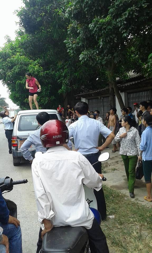 Người phụ nữ nhảy lên nóc xe chở lãnh đạo huyện nhảy múa 1