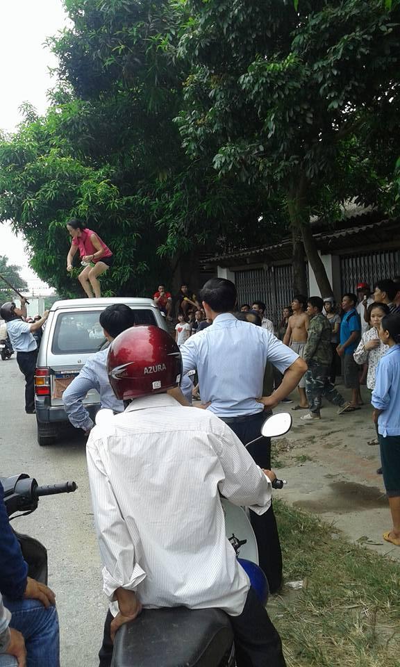 Người phụ nữ nhảy lên nóc xe chở lãnh đạo huyện nhảy múa 3
