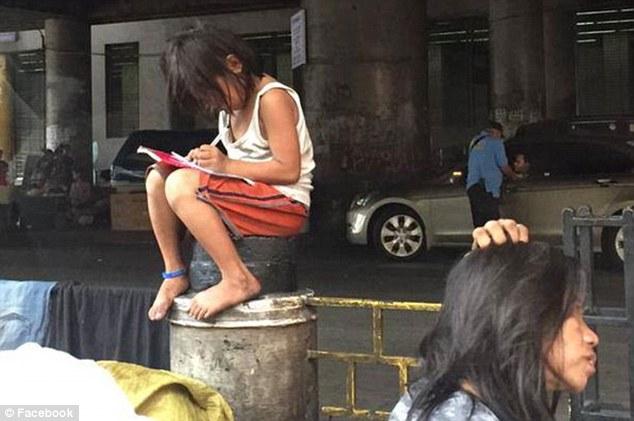 Bức ảnh bé gái lem luốc ngồi học trên phố gây chấn động Philippines 1