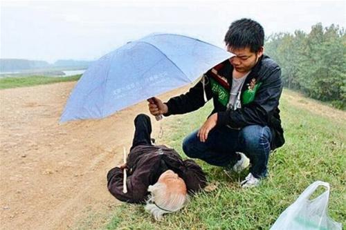 Chàng trai dầm mưa che ô cho bà cụ bị gãy chân gây xúc động 1