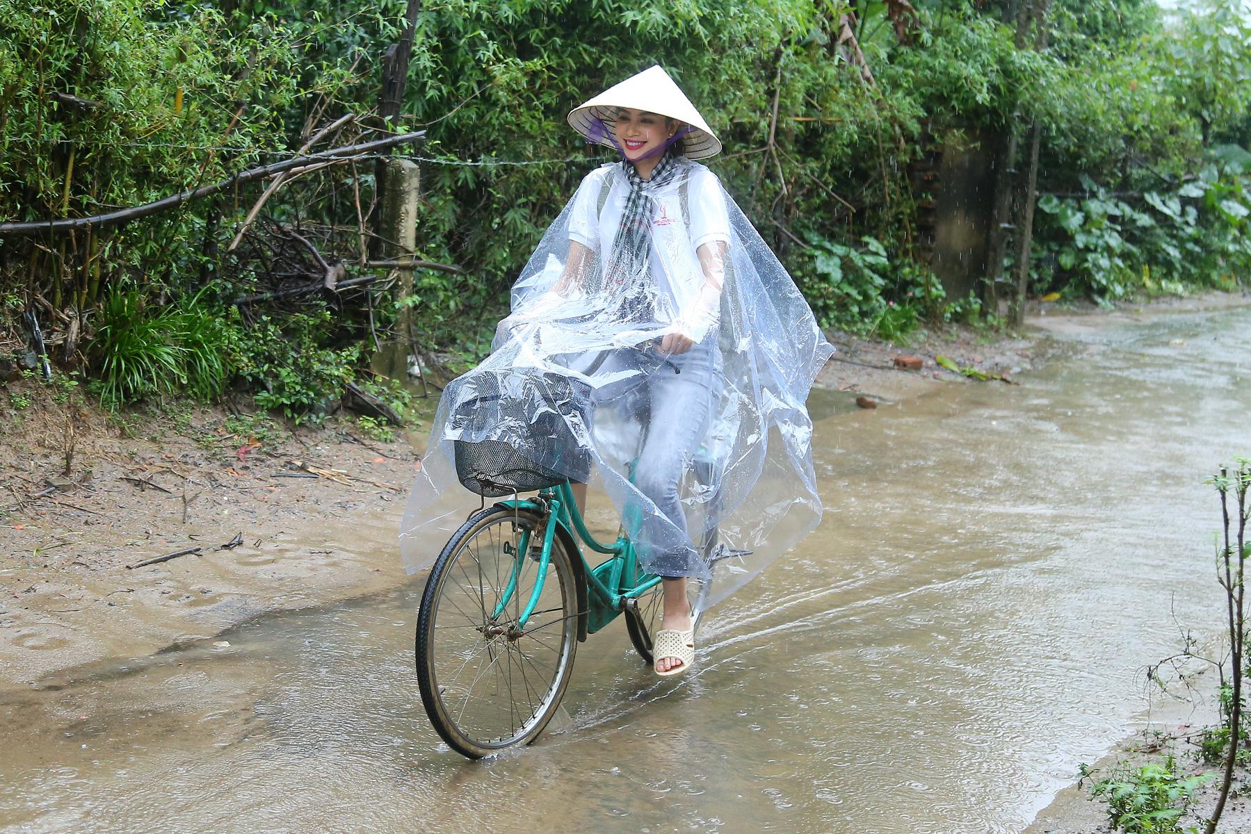 Hoa hậu Phạm Hương chạy xe đạp chở cụ già trong cơn mưa dầm 1