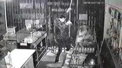 Camera ghi lại cảnh trộm đu dây như xiếc vào cửa hàng trộm điện thoại 1