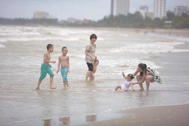 Hình ảnh Chùm ảnh: Bất chấp sóng to gió lớn sau bão số 2, nhiều gia đình vẫn đưa trẻ em ra tắm biển Cửa Lò số 7