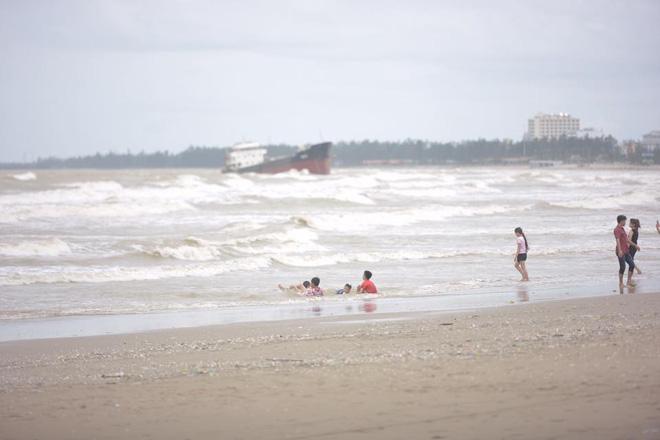 Hình ảnh Chùm ảnh: Bất chấp sóng to gió lớn sau bão số 2, nhiều gia đình vẫn đưa trẻ em ra tắm biển Cửa Lò số 9