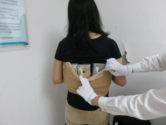 Một phụ nữ bị bắt vì buôn lậu hơn 100 chiếc iPhone và đồng hồ Tissot bằng cách quấn quanh cơ thể 1