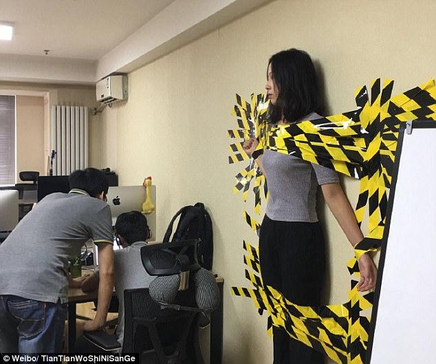 Vi phạm nội quy công ty, cô gái trẻ bị dán băng keo dính chặt vào tường 2