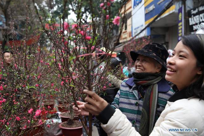 Hình ảnh không khí Tết rộn ràng khắp phố phường Hà Nội tràn ngập các trang báo Trung Quốc - Ảnh 1.