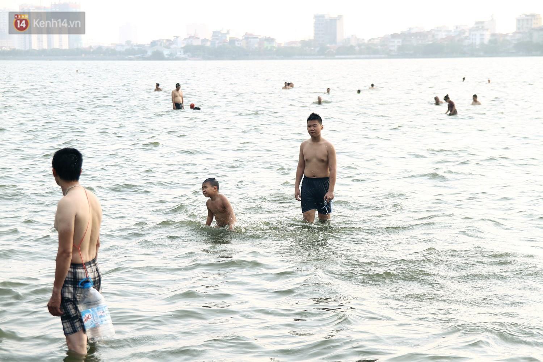 Nắng nóng oi bức, người dân Thủ đô bế chó cưng ra Hồ Tây cùng tắm để giải nhiệt dù có biển cấm - Ảnh 2.