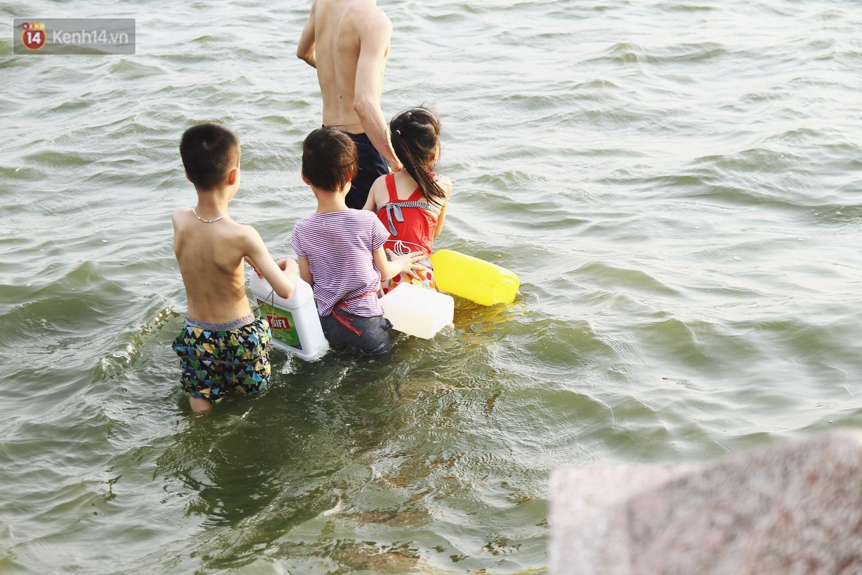 Nắng nóng oi bức, người dân Thủ đô bế chó cưng ra Hồ Tây cùng tắm để giải nhiệt dù có biển cấm 13