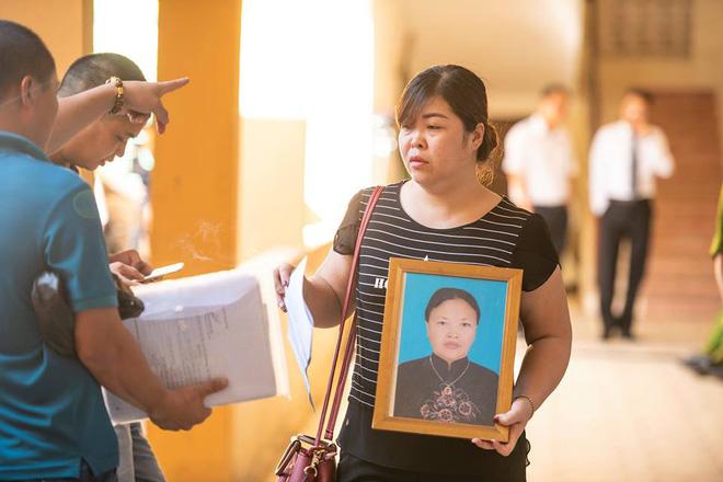 Người thân mang di ảnh các nạn nhân tử vong khi chạy thận tại BV Đa khoa Hòa Bình đến phiên tòa.
