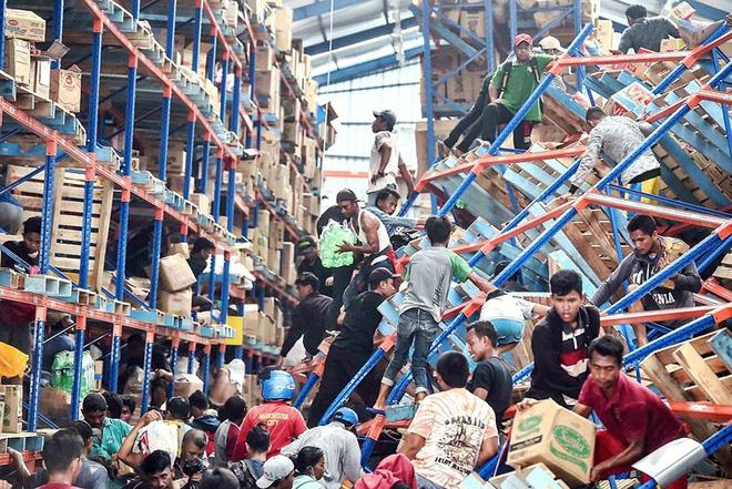 24h qua ảnh: Người dân cướp bóc tìm thức ăn sau thảm họa sóng thần ở Indonesia - Ảnh 3.