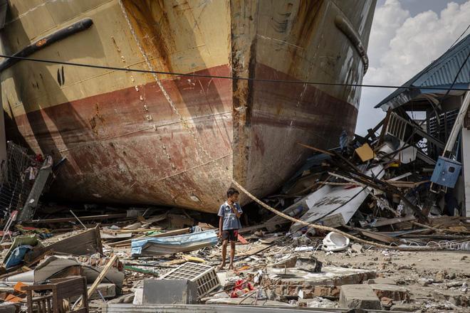 24h qua ảnh: Người dân cướp bóc tìm thức ăn sau thảm họa sóng thần ở Indonesia - Ảnh 8.