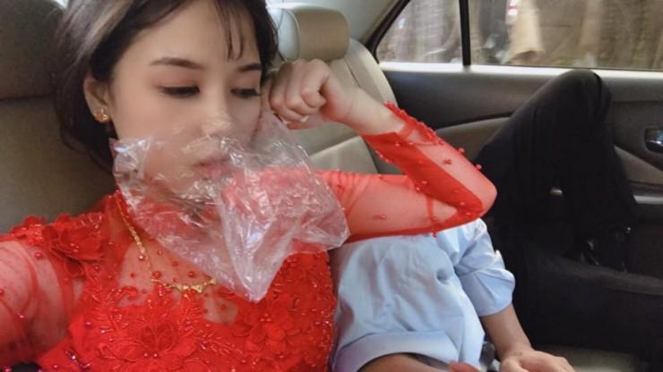 Hình ảnh cô dâu say xe bịt mũi bằng giấy ăn, đeo túi bóng trên miệng nhưng trước khi