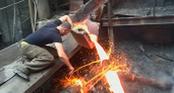 Người đàn ông đập tay trần vào dòng kim loại nóng chảy mà không bị bỏng