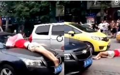 Lao vào xe ô tô đang chạy, cô gái nằm bất động ăn vạ trước mũi xe