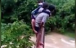 Video sốc: Người đàn ông bám dây cáp cõng học sinh qua lũ dữ