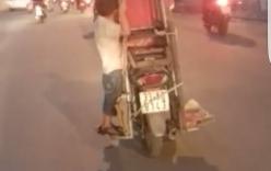 Rùng mình cậu bé 5 tuổi bám vào khung gỗ trên xe máy đang chạy