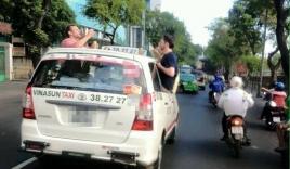 Du khách Tây nhậu trên nóc xe taxi đang chạy ở Sài Gòn