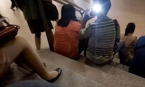 Vờ nghe điện thoại, nam thanh niên lén chụp ảnh cô gái mặc váy hớ hênh trên cầu thang
