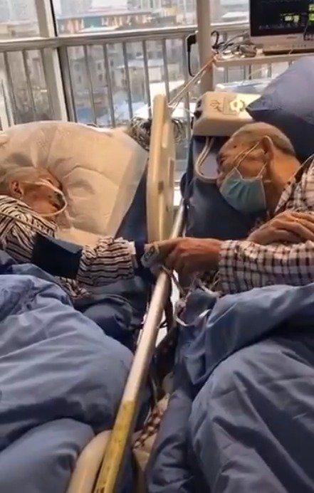 Vợ chồng già hơn 80 tuổi nhiễm virus corona nắm chặt tay nhau trong phòng bệnh 1